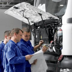 A group of mechanics working on a truck in the workshop