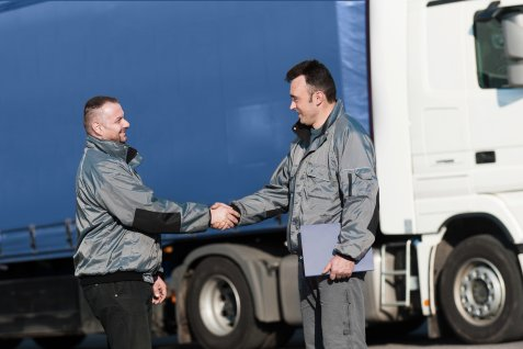 Two men shaking hands in front of a truck